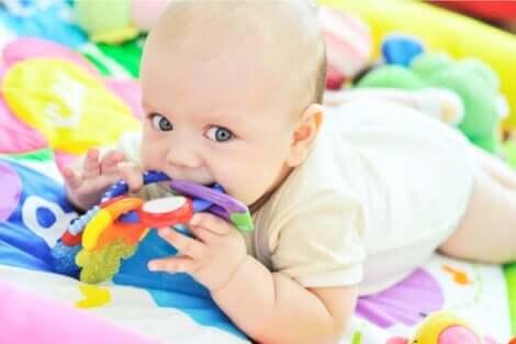 En baby som leker og jobber med sensorisk utvikling.