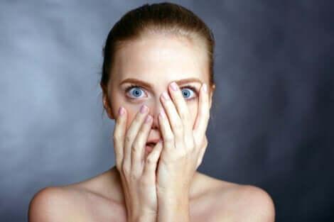 En kvinne med blå øyne som dekker til ansiktet.