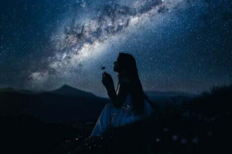 En kvinne med en blomst om natten.