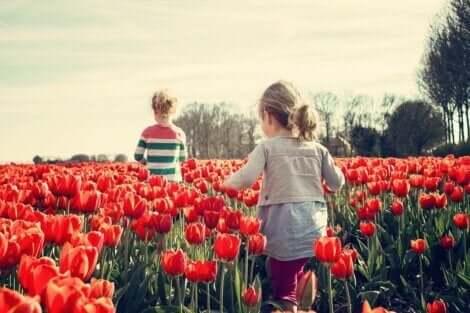 To barn som går gjennom en eng av tulipaner og lærer sosioemosjonelle ferdigheter.