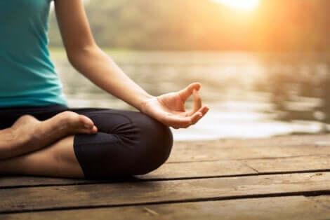 En kvinne som mediterer på en brygge.