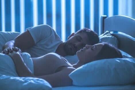 En mann og en kvinne som ligger i sengen.