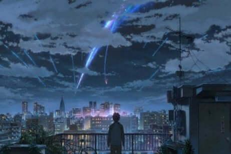 En ung person som ser over en by som ser ut til å ha meteorer som faller fra himmelen.