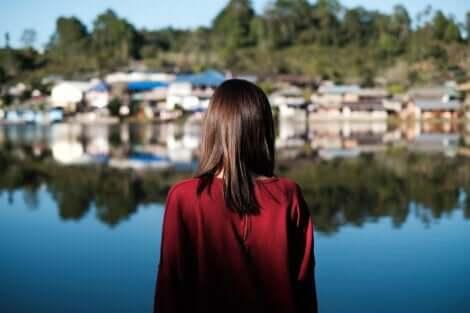 En kvinne som ser over en innsjø mot en liten landsby.