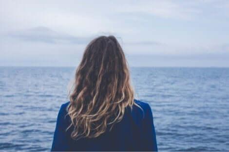 En kvinne som ser ut mot havet.