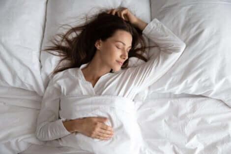En kvinne som sover godt i sengen.