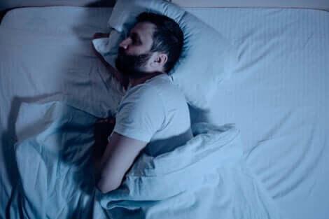 En sovende mann på siden i sengen.