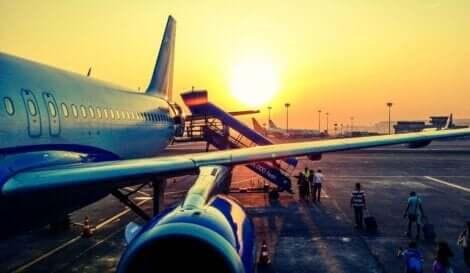 Folk som går ombord på et fly ved solnedgang.