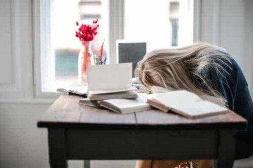 En kvinne som sover på pulten sin.