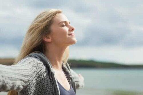 En kvinne som vender ansiktet mot solen.