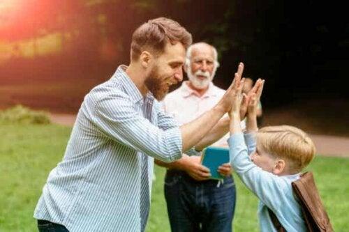 En mann som gir high five til et barn.