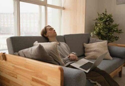 En mann som sover på sofaen med laptop på fanget.