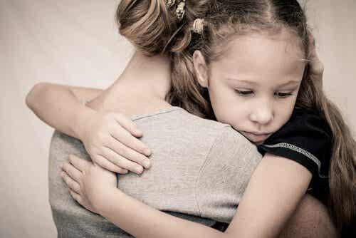 En kvinne klemmer en liten jente