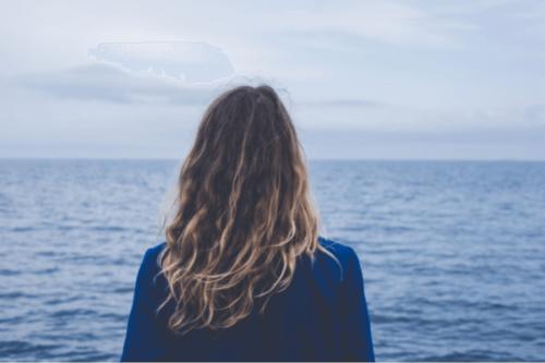 Kvinne som ser ut mot havet.