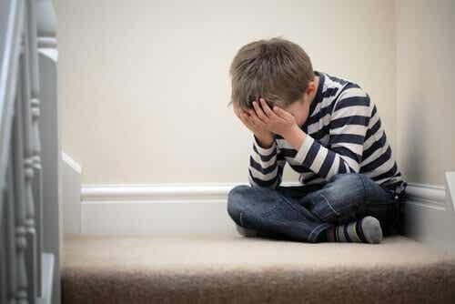 En liten gutt med angst sitter på trappen