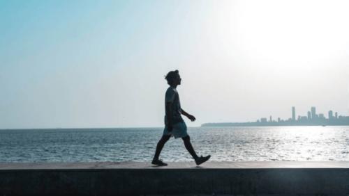Mann som går langs havet.