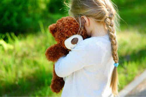 En jente som klemmer bamsen sin.