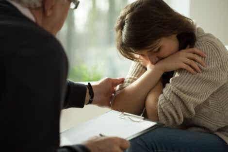 En kvinne som gråter mens hun snakker med en psykolog.