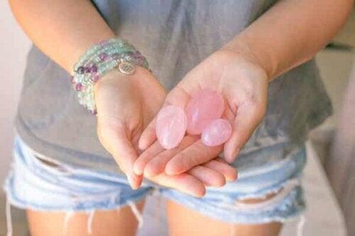 En kvinne som holder tre eggformede steiner.