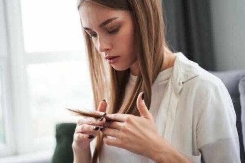 En kvinne som ser på håret sitt.