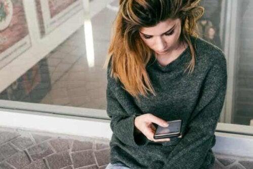 En kvinne som ser på telefonen sin.