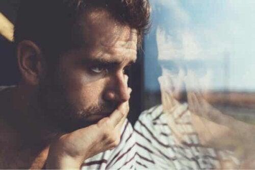 En mann som ser ut av vinduet.