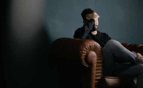 En mann som sitter på en sofa og føler seg bekymret.