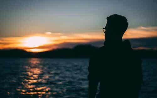 En mann som tenker på viktigheten av å være medfølende med seg selv mens man ser på havet.