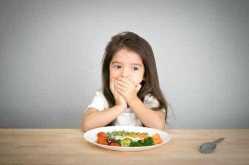 Et barn som dekker munnen.