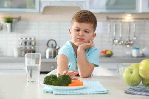 Et barn som skyver bort en tallerken.