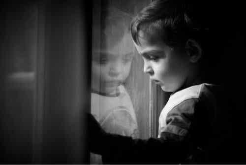 Et trist barn som ser ut av vinduet.