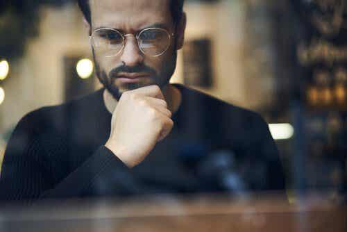 En fyr med briller som tenker i et vindu
