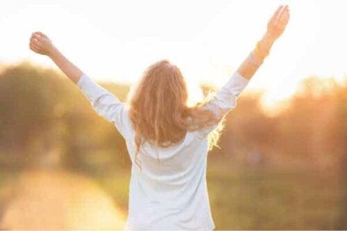 En kvinne som holder opp armene.