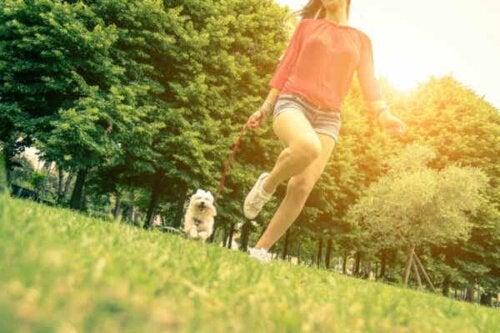 En kvinne som løper med en hund.