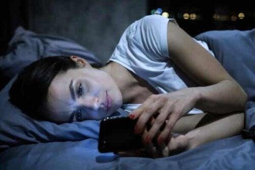 En kvinne som ser på mobiltelefonen sin.