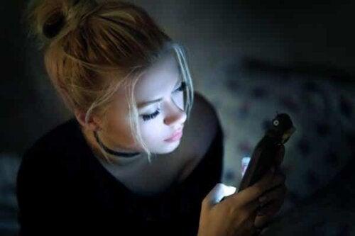 En kvinne som skriver på mobiltelefonen sin.