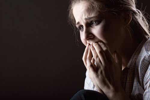 En redd kvinne som dekker munnen med hendene.