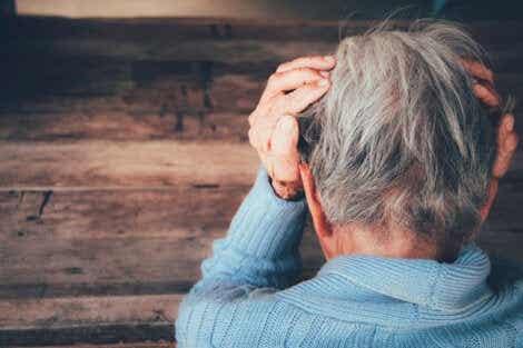 En kvinne med frontotemporal demens stirrer på gulvet.