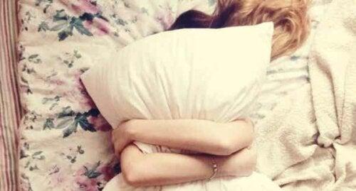 Kvinne som sover med en pute.