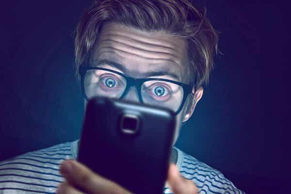 En mann som ser på en telefon som viser morbid nysgjerrighet