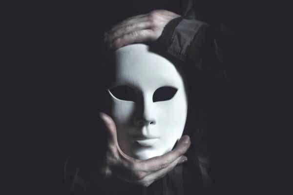 Hender som holder en maske