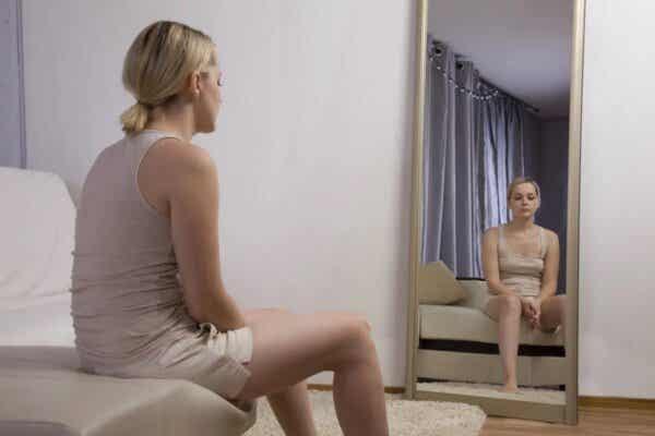 En trist kvinne som ser seg i speilet
